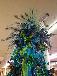 Large peacock-inspired tree topper with lots of blue and green ribbon - Decoist