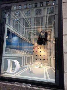 This is very creative Dior window. It shows the top view perspective of a room. It attracts attention because it is very odd perspective. And the overall colours of grey and white adds brand image of sophistication and the contrast with the outfit and shoes of the mannequin adds the highlight. This inspires to go beyond the box and think differently about display; it doesn't always have to be front (or side)  view.