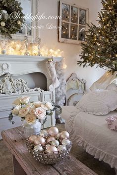 This shabby chic living room decorated for Christmas is stunning. A simple Christmas tree, glass ornament decor, & a lit up mantel just put us in the holiday spirit!