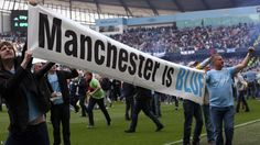 The City fans invade the pitch in celebration, and unruffle a banner to show who the leading club in Manchester is now