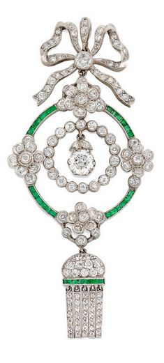*An Edwardian diamond and emerald pendant set to the centre with an old brilliant-cut diamond estimated to weigh half a carat hanging to the centre of an old brilliant-cut diamond-set surround surrounded by four diamond-set flowers joined together by calibre-cut emerald-set links, with diamond-set bow top and diamond and calibre-cut emerald-set fringe at the bottom, circa 1910