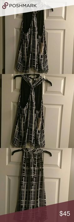 Beautiful sheer Kenneth Cole Top Kenneth Cole sheer black,white and gray blouse. Criss cross in the front at the top. The back has buttons at the top. Very pretty. Kenneth Cole Tops Blouses