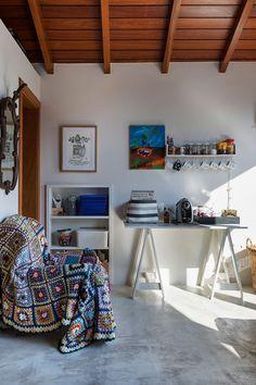 Decoração com personalidade, decoração colorida com obras de arte, móvel de madeira, teto de madeira, canecas, manta colorida e luz natural.