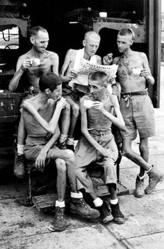 Japan - War Crimes British soldiers liberated from a Japanese POW camp in Sumatra sit on the steps of an Allied ambulance reading about and discussing the American atomic bomb being dropped on Hiroshima.