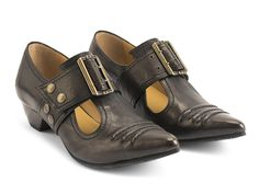 """A super pointy-toed, buckled t-strap loafer with stitched wrinkled leather on the instep, The Pilgrim shoe was one of John's first women's designs which took its initial inspiration from the Victorian era. The updated design includes a rubber sole plate, a1.25"""" leather wrapped heeland features specialtyleathers that willage gracefully. The Pilgrim is an ode to John's humble beginnings, his values which he still aspires to, and a great testament to the genius we celebrate...."""