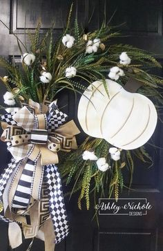 """This 18"""" grapevine wreath is adorned with preserved cotton bolls, grasses, a white pumpkin and rustic neutral ribbon.This Cotton Boll and White Pumpkin Neutral Wreath looks great on any home. This wreath is built on an 18"""" round grapevine."""