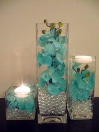 who doesn't love floating candles? So majestic! but seriously, how about candles with glittery water? and instead of just glass rocks throw in some champagne corks with gems and fancy stuff!