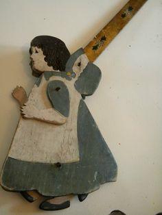 This old folk art toy piece has multiple feet that turn on a wheel mechanism inside as she walks forward.