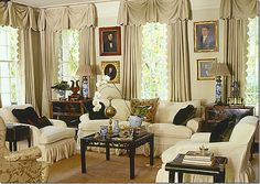 """Scallop-edged curtains, """"ancestor"""" paintings, blue and white lamps and accessories on the coffee table, slipcovered furniture, sisal carpeting - Jackye Lanham"""