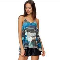 """CAMEO BROKEN STRINGS TOP IN CAMO PRINT CAMEO BROKEN STRINGS TOP IN CAMO PRINT  The PERFECT layering piece. Of course it looks amazing on it's own as well! The Cameo camo print Broken Strings top is a loose, floaty style tank top with thin straps and draped panels under the arms. The top features a thin racer back design.  Size & Fit: Large Model Wears: Size Small Height: 180cm / 5' 11 Bust: 33 / 84cm Waist: 24"""" / 61 cm Hips: 34.5"""" / 87 cm"""" MAIN: 100%POLYESTER LINING: 100%POLYESTER CAMEO Tops…"""