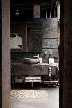 un meuble vasque en bois vieilli et un vasque en pierre dans la salle de bains rustique