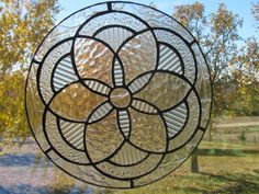 This suncatcher is made of different textures of clear glass. These symmetric shapes are pleasing to the eye. This will add charm to any