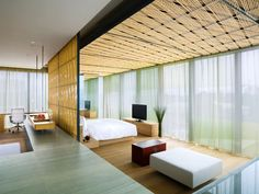 Amazing and Fantastic Minimalist Home Design with Bamboo Wall Decor, Bamboo Ceiling, Master Bed, Home Office Chair, and White Coffee Table