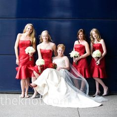 The bridesmaids wore red satin, tea-length dresses that mimicked the cut and style of the bridal gown, but with a shorter hemline.