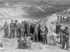 Mass grave in the dunes at Waalsdorp, The Netherlands. Dutch collaborators and German war criminals are forced to exhume executed resistance fighters. Dutch police and Canadian soldiers  supervise. August 1945.