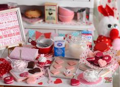 Enjoy a tasty Valentines Day with these cream-filled sandwich cookies! Included in this set is a worn baking sheet of cherry chip cookies waiting to be prepped, box of powdered sugar, bowl of pink buttercream frosting, bowl of white buttercream frosting, red velvet cupcake, shabby pink-handle spatula and a shabby pink cutting board with cookie shells on it. A plate of red velvet and cherry chip sandwich cookies completes this set. All other items for decorative purposes and not included…