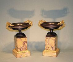 A pair of early 19th Century bronze and ormolu Tazzas having ball and reeded rims and gothic stems with double leaf scroll handles raised on Sienna marble plinth bases with ormolu borders.   Circa: 1830