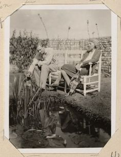 John Lehmann and Virginia Woolf sitting on a bench near a pond. Monk's House (Rodmell, England), undated.