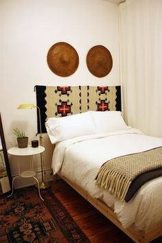 A Rug Headboard looks great and is cheap. Make a faux headboard with a vintage tex mex woven rug, or any rug that shows off your style. | fabuloushomeblog.comfabuloushomeblog.com