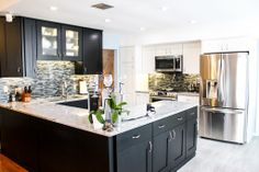 The contrast of the white countertop with the black cabinetry is very sharp. The backsplash is a great accent for the kitchen!  Bridgewood Advantage, Fontana door style, Black finsih, LED cabinet lighting, Viscount White granite countertop