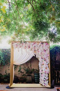 Golden Wedding Arch Draped With Florals // http://www.deerpearlflowers.com/vintage-frames-wedding-decor-ideas/