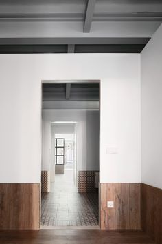 Each room of this apartment is decorated in three bands: a grey vaulted ceiling at the top, a section of white-painted wall in the centre, and a contrasting flooring with matching wainscotting at the bottom.