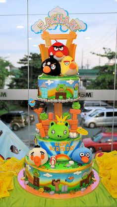 Angry Birds cake    I love how colourful this one is!    It looks like they used cookies for a lot of the decoration on top of airbrushing the tiers.   Nice use of plushies too (if you are into mixing non-edibles with your edibles).