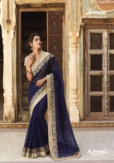 Alluring navy blue jacquard saree with heavy resham work border and rawsilk blouse.