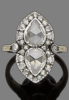 An early 19th century diamond dress ring. The two pear-shaped rose-cut diamonds set opposite to each other, within similarly-cut diamond border and shoulders, later shank.