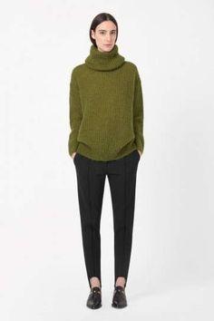 Maglione verde - Cos, look con pantaloni neri e maglione a collo alto.