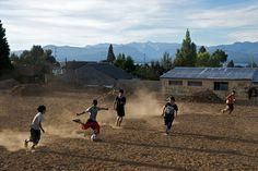 Kids Playing Soccer on Dirt Field