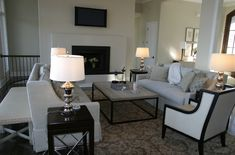 Elegant gray & black living room design with oatmeal linen curvy skirted sofas, brickmaker's coffee table, silver lamps, ivory & black wingback chairs, ivory bench with nailhead trim, modern fireplace and glossy ebony end tables.