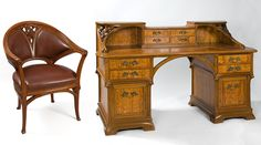French Art Nouveau Desk and Armchair by Gauthier & Poinsignon  A French Art Nouveau desk and armchair suite by Camille Gauthier & Paul Poinsignon, featuring organically stylized carved French oak with a veneer of Hungarian ash, intricate bronze drawer pulls and a hand-embossed leather surface. The desk and chair both have the same carved and pierced flower design. Circa 1900