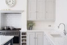 Sustainable Kitchens - Bright Open Plan Family Kitchen in London. Oak shaker style cabinetry painted in Farrow & Ball Ammonite with built in spice racks next to the Smeg range cooker. The worktop is Bianco Fantasia. The extractor is housed in the chimney breast and has a cornice style shelf for decorative items.