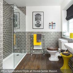 Hier führen knallige Farbakzente zu einer hübschen Badezimmer-Idee. Handtuch, Hocker und das Accessoire auf der Fensterbank sind in gelb aufeinander…