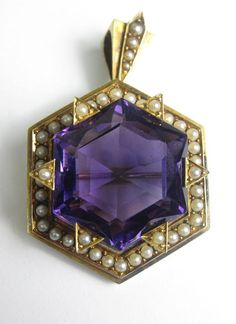 A Victorian amethyst and seed pearl brooch/pendant.  The central hexagonal-cut amethyst to raised triangular pearl-set claws, the hexagonal mount set with row of seed pearls, surmounted by a stepped bale also set with seed pearls, length 45mm, pearls untested, to original fitted case retailed by R. Stewart, Glasgow