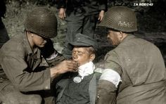 American soldiers help a wounded German.