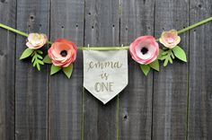 This beautiful garland is made of four handcrafted paper flowers and leaves made of card stock and lighter weight pattered paper attached to a light green ribbon. The flag banner is hand lettered in gold and can be personalized to say anything for your occasion! Please specify your wording choice in the comments at checkout. The flowers and the flag banner are 24 inches in length, and there is an additional 20 inches of ribbon on each end for hanging. The flag is made of a natural colored…