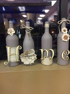 """This wine bottle set features home spelled out, all four wine bottles are refurbished and spray painted and gray/purple color and decorated. These are customizable, and made to order. bottle crafts wedding Items similar to Wine bottle set """"Home"""" on Etsy Glass Bottle Crafts, Wine Bottle Art, Diy Bottle, Glass Bottles, Vodka Bottle, Wine Glass, Bottle Garden, Plastic Bottle, Perfume Bottles"""