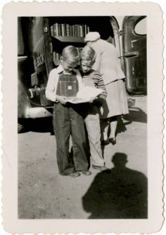 Johnston County, NC bookmobile and two boys reading a book, November 1946 :: Library History Collection