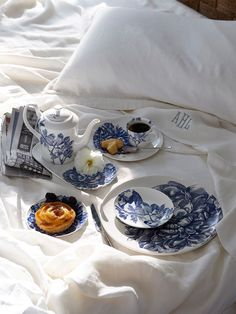 A charming breakfast in bed includes the daily news paper, tea, coffee, danishes, croissants, and tea adorned on top of blue and white ceramic.