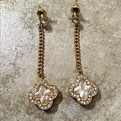 Gold tone brilliant clover rhinestone earrings! Stunning with beautiful beveled clover shaped beads in center surrounded by rhinestones extended from a gold tone chain and a rhinestone at top! Jewelry Earrings