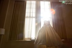 Wedding dress hanging in window - Sun flare - Sassy Mouth Photography - Wedding Photography