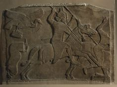 Gypsum wall panel relief:Neo-Assyrian   Date728BCTwo Assyrian cavalrymen charging against enemies. Both have short curly hair, pointed beards, and wear a kind of pointed helmet with earflaps. The first horseman wears a fringed tunic, highly ornamented with discs set in squares, and a cuirass. The horses have the usual triple tasselled decoration on top of their heads, and two tassels attached to their plaited collars. The second horseman is spearing the horse of an enemy which is sinking…