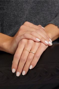 Simple nails with a few dainty gold rings.