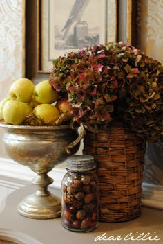 Hydrangeas, apples, and acorns in basket, silver, and glass