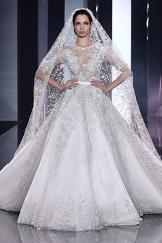 Off-white silk tulle bridal gown with metallic printed lace underskirt and crystal, pearl and floral oyster embellishment with coordinating veil.