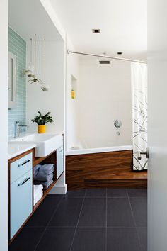Bathroom inspiration.  modern bathroom by Portal Design Inc  The blue portion of the vanity is lacquered MDF, while the wood elements here and on the tub surround are walnut.