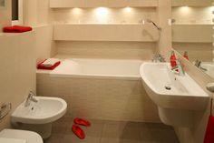 Jasne kolory, duże lustro na ściane nad umywalką i podświetlone nisze sprawiły, że mała łazienka wydaje się większa. Projekt: Izabela Szewc. Fot. Bartosz Jarosz