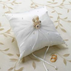 "Beach Theme Ivory Seashell Pillow for Rings  This ivory satin ring pillow measures 7"". A scattering of pearls decorate the front, with a white sheer ribbon wrapped around the middle and tied by a cluster of seashells. Two thin white ribbons hang from the seashell cluster for ring placement. Large and small pearls serve as tassels for all four corners of this pillow."